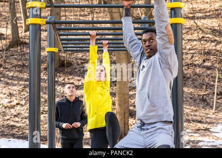 Les amis de l'exercice à barres dans un parc Banque D'Images