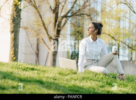 Young businesswoman en pause, à l'aide d'un ordinateur portable, assis dans l'herbe et boire du café