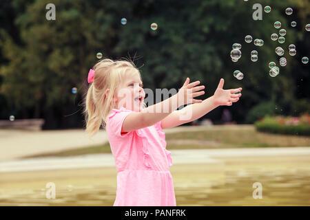 Fille de trois ans jouant avec des bulles de savon