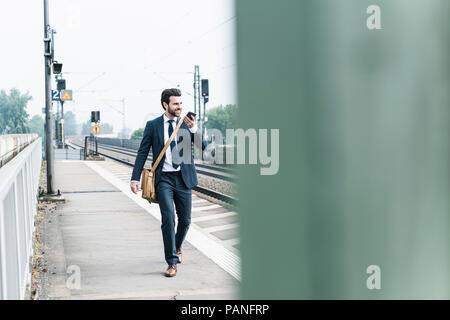 Smiling businessman with cell phone marche à la plate-forme Banque D'Images