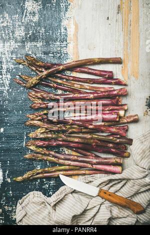 Asperges violettes fraîches sur fond de bois rustique, composition verticale