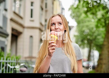 Jeune femme bénéficiant d'un cornet de crème glacée dans la ville Banque D'Images