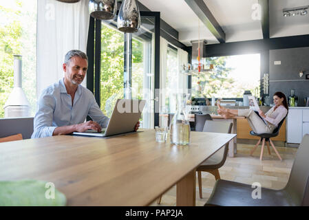 L'homme souriant à la maison à l'aide d'un ordinateur portable à table avec woman in background reading newspaper Banque D'Images