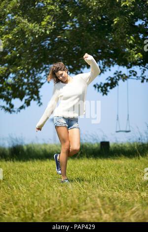 Jeune femme sautant autour on meadow Banque D'Images