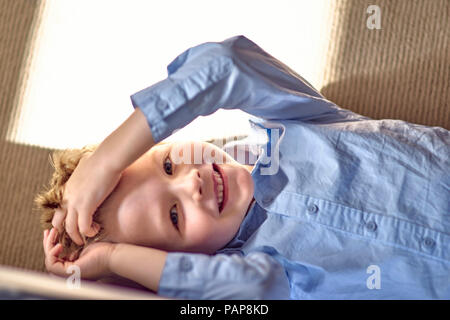 Portrait of happy boy lying on couch Banque D'Images