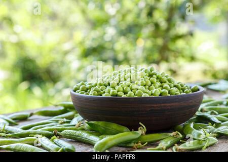 Pois verts pelées dans une assiette sur une table en bois. Il se trouve à côté de gousses de pois. Photo battante Banque D'Images