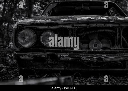 Vieille voiture accidentée en noir et blanc. Voiture rouillée abandonnée dans la forêt. Vue avant du gros plan en décadence et Rusty wrecked voiture abandonnée. L'art de Banque D'Images