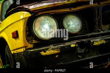 Vieille voiture accidentée dans un style vintage. Voiture jaune rouillé abandonné dans la forêt. Libre vue avant phares des épaves rouillées voiture abandonnée. L'art d'une Banque D'Images