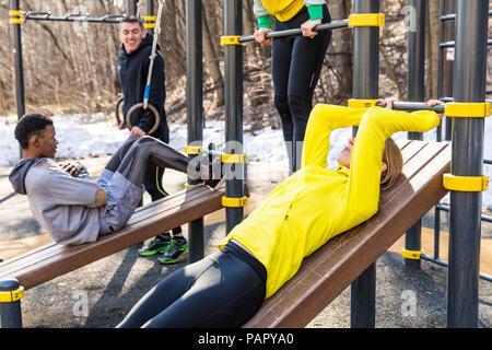 Les amis de l'exercice à l'équipement de conditionnement physique dans un parc Banque D'Images
