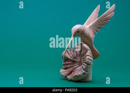 Un colibri en bois sculpté atterrissage sur une coquille en bois ouverte, sur un fond vert Banque D'Images