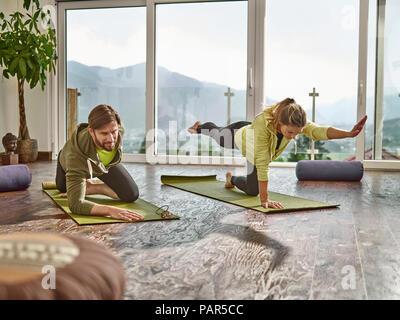 Couple practicing yoga dans une chambre avec fenêtre de panorama Banque D'Images
