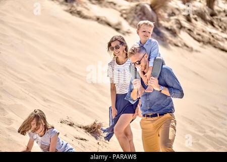 Famille heureuse marche sur la plage ensemble Banque D'Images