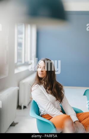 Jeune femme assise dans une chaise, regardant par la fenêtre de
