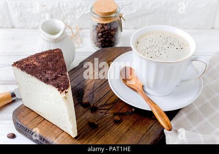 Tasse de café avec gâteau au fromage ou fromage doux dans le café blanc sur fond de bois ancien, vue du dessus, copiez spase Banque D'Images