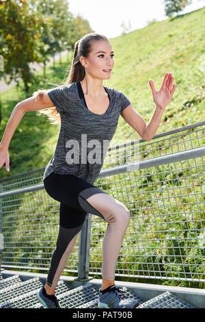 Jeune femme tournant sur des escaliers dans un parc Banque D'Images