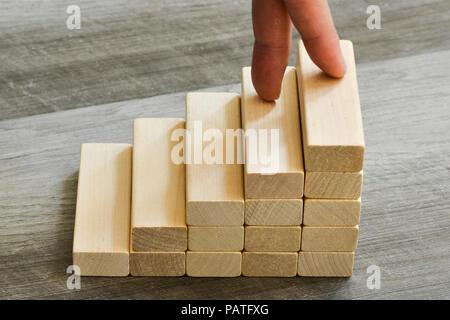 Les doigts jusqu'à l'escalade de haut sur l'escalier en bois - Concept de réussite Banque D'Images