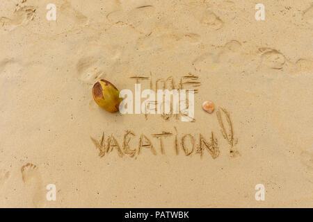 Concept de vacances exotiques. Temps pour locations écrit sur le sable avec des noix de coco et footprints Banque D'Images