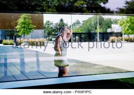 Jeune femme debout par une fenêtre d'un bâtiment de verre Banque D'Images