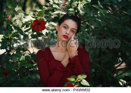... Portrait de jeune femme habillée en rouge dans le jardin urbain Banque  D Images fab06ad506d