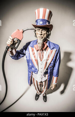 Comité permanent de l'Oncle Sam avec une pompe à essence nourrissant qui a eu lieu en face de lui. Shot conceptuel décrivant la dépendance américaine au pétrole / gaz / pétrole.