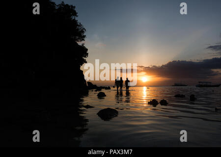 3 jeunes hommes à marcher le long du bord de l'eau sur la plage de l'île magnifique aux Philippines. Banque D'Images