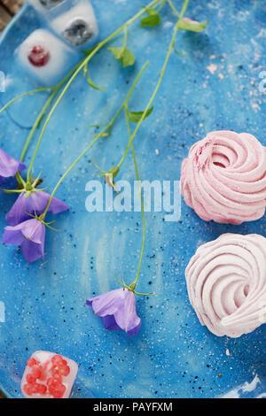 Le marshmallow sur un ciel bleu. Dessert léger.délicates fleurs sauvages. Et petits fruits congelés dans la glace Banque D'Images