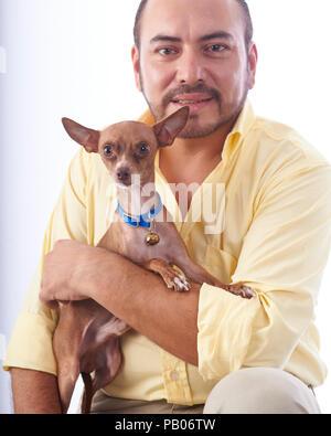 Studio portrait sur un fond blanc d'un homme dans une chemise jaune, tenant un chihuahua chien dans ses bras Banque D'Images