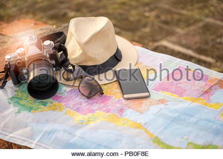 Voyage Voyage autour du monde concept, appareil photo vintage hat sungrass et smartphone sur la carte Banque D'Images