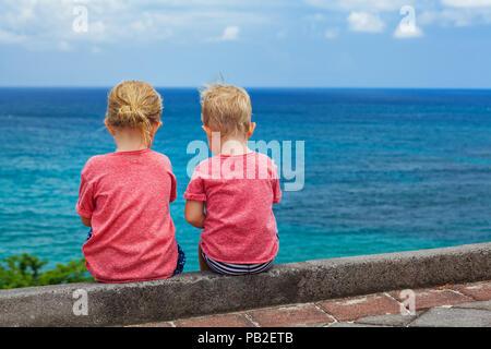 Heureux les enfants s'amuser sur la plage à pied. Couple d'enfants assis sur la falaise, de parler, de regarder et de surf mer ciel bleu. Style de voyage, les activités de plein air en f Banque D'Images