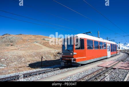 Tram train rouge ou sur le transport ferroviaire à Matterhorn, Zermatt Alpes pic à la population, la Suisse, l'Europe avec ciel bleu clair Banque D'Images