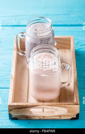 Des fraises fraîches et de blueberry milk-shakes sur tableau bleu.