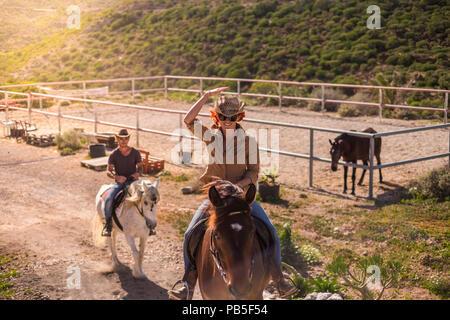 Couple de rider l'homme et la femme avec Brown et chevaux blancs rendez-vous et profitez de la piscine en plein air activité de loisirs dans les montagnes voyage excursion cowbo moderne. Banque D'Images