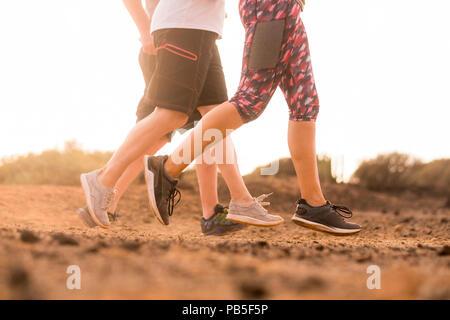 Groupe de trois caucasian runner doing jogging sur le sol du désert de l'activité en plein air dans la nature. Sport et mode de vie sain pour les gens de l'été soleil météo. Banque D'Images