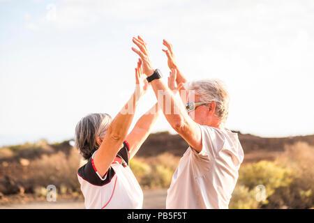 Couple senior profiter et gagner ensemble donner cinq et s'étreindre sous un beau temps, jour de soleil en été. L'activité sportive et des vêtements. D'âge actif Banque D'Images