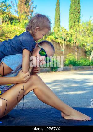 Portrait d'une belle maman et son fils jouer jeux de sport dans le parc aux beaux jours de l'été, heureux de l'enfance active, une bonne famille aimante concept Banque D'Images