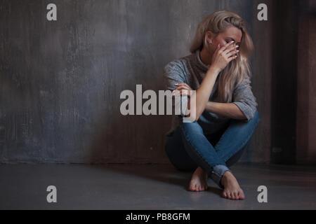 Femme triste. fille blonde assise sur le sol, la tristesse et la dépression, concept de problème psychologique Banque D'Images