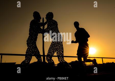 27 juillet 2018, l'Allemagne, Berlin: un jogger passe devant la rivière Spree en face de Jonathan Borofsky sculpture de trois personne pendant le lever du soleil. Les personnages masculins, aussi appelé l'homme molécule, sont d'environ 30 mètres de haut et se tiennent au milieu de la Spree. Photo: afp/Assanimoghaddam Mohssen Banque D'Images