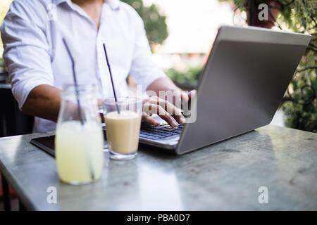 Les jeunes afro-américains attractive businessman sitting in cafe bar, boire du café et avoir fait quelques travaux sur ordinateur portable. Banque D'Images