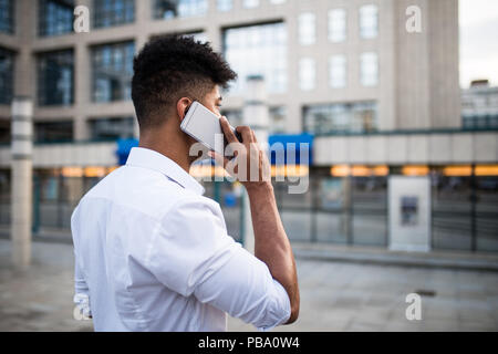 Beau jeune homme afro-américain debout devant d'énormes capacités d'affaires moderne; sourire et parler sur téléphone mobile.