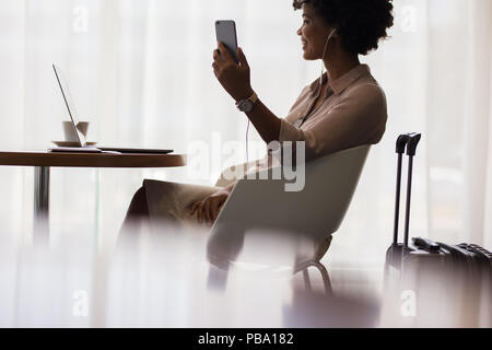 Heureux femme faisant appel vidéo de téléphone mobile tout en restant assis à l'aéroport salon. Femme d'affaires en attente de voyage a l'aéroport et à l'aide de smart phone. Banque D'Images