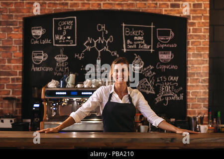 Portrait of female barista debout derrière comptoir. Femme cafe owner in apron looking at camera et souriant. Banque D'Images