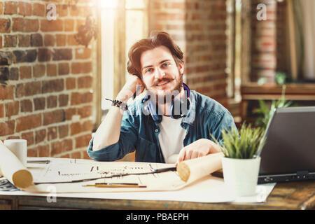 Architecte barbu homme souriant à la caméra assis à son bureau au bureau à travailler sur des plans de l'élaboration de projets d'ingénierie la créativité copyspace occupation travailleur entrepreneur réussi de carrière. Banque D'Images
