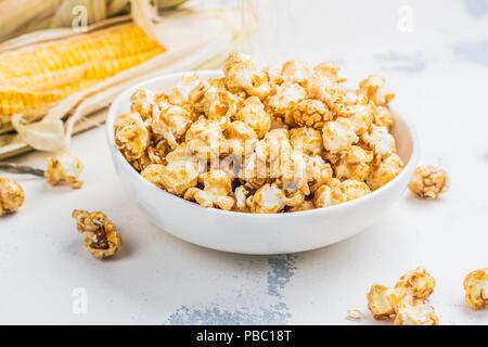 Maïs soufflé au caramel dans un bol blanc Banque D'Images