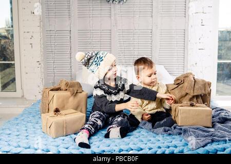 Thème Le matin de Noël. Deux enfant Young boy and girl frère et soeur sont assis sur le lit dans une étreinte avec un sourire et la joie sont l'ouverture de nouveaux Banque D'Images
