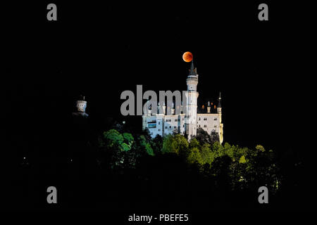 Hohenschwangau, Allemagne. 27 juillet 2018. Une éclipse lunaire, Lune de sang dans le ciel au château de Neuschwanstein (construit par le roi Louis II, 2ème, vu à Hohenschwangau près de Füssen, en Bavière, Allemagne, le 27 juillet 2018. La lune déplacé dans l'ombre de la terre. Avec 1 heure, 43 minutes, son la plus longue éclipse lunaire au 21ème siècle, © Peter Schatz / Alamy Live News Banque D'Images