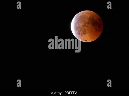 Hohenschwangau, Allemagne. 27 juillet 2018. Un avion passe la Lune de sang, éclipse de lune dans le ciel au château de Neuschwanstein (construit par le roi Louis II, 2ème, vu à Hohenschwangau près de Füssen, en Bavière, Allemagne, le 27 juillet 2018. La lune déplacé dans l'ombre de la terre. Avec 1 heure, 43 minutes, son la plus longue éclipse lunaire au 21ème siècle, © Peter Schatz / Alamy Live News Banque D'Images