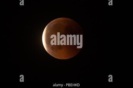 Berlin, Allemagne. 27 juillet, 2018. 27.07.2018, Berlin: la lune s'allume en rouge pendant l'éclipse lunaire totale, tandis que l'obscurité diminue lentement. Crédit: Paul Zinken/dpa/Alamy Live News Banque D'Images