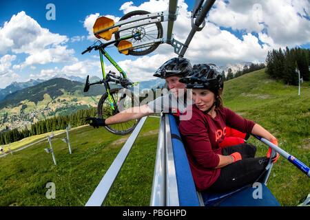 Un couple d'un télésiège en transportant un VTT dans la station alpine de La Clusaz au cours de l'été. Banque D'Images