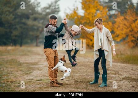 Heureux parents s'amuser et élèvent leur fille au chemin forestier en regard de chien sautant au cours de marche en forêt d'automne.