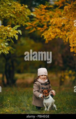 Fille de l'enfant est assis et joue avec son chien au cours de marche en forêt d'automne. Banque D'Images